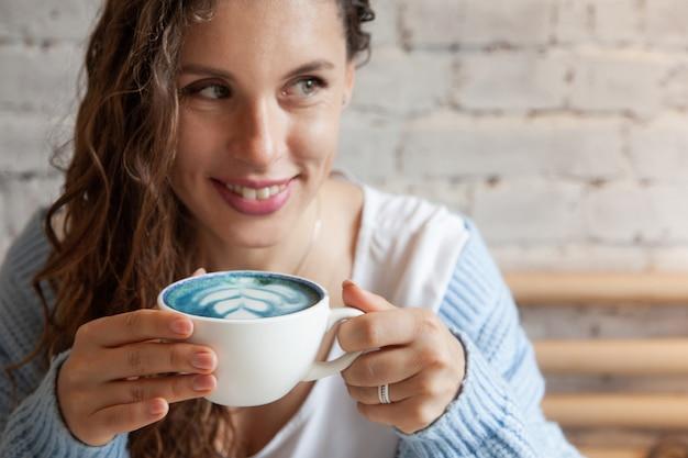 Glückliche junge frau im gestrickten warmen pullover, der mit den händen eine tasse des gesunden heißen blauen kaffee latte hält. blauer kaffee latte mit frischen kaffeebohnen und bluechai schmetterling erbsen tee gemacht. wohlfühlkonzept.