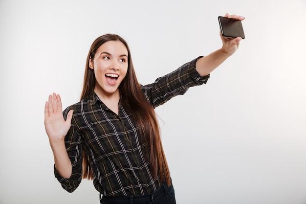Glückliche junge frau im hemd, das selfie am telefon macht