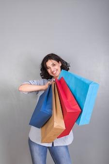 Glückliche junge frau im hemd mit einkaufstaschen