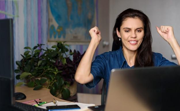 Glückliche junge frau im jeanshemd, das nach hause mit einem laptop arbeitet und ihre arme nach oben streckt