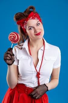 Glückliche junge frau im pin-up-stil mit süßigkeiten lutscher