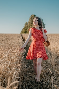 Glückliche junge frau im roten kleid mit brot und laib in der nettoeinkaufstüte