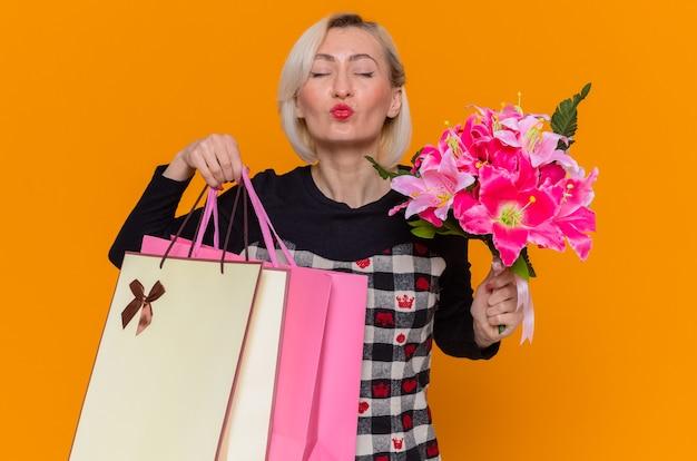 Glückliche junge frau im schönen kleid, das blumenstrauß von blumen und papiertüten mit geschenken hält, die einen kuss blasen, der internationalen frauentag feiert, der über orange wand steht