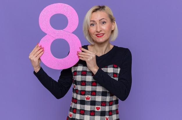 Glückliche junge frau im schönen kleid, das nummer acht aus pappe betrachtet, die vorne lächelnd fröhlich feiert internationalen frauentag, der über lila wand steht