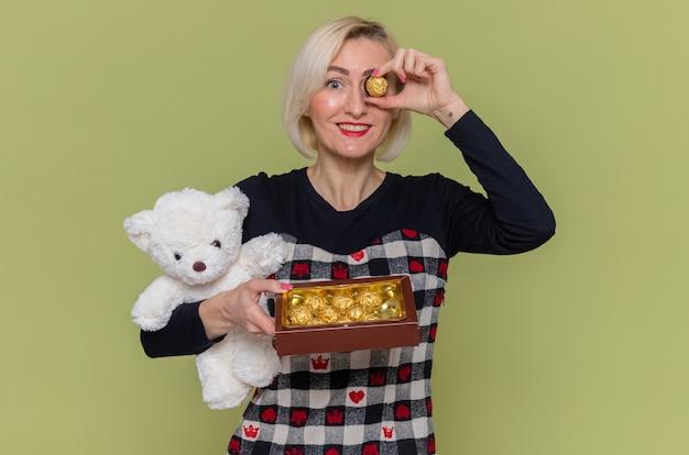 Glückliche junge frau im schönen kleid, das teddybär und pralinen als geschenke hält, die fröhlich den internationalen frauentag feiern, der über grüner wand steht