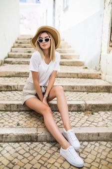 Glückliche junge frau im sommerhut, der auf der treppe in der stadtstraße sitzt