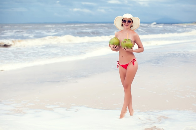Glückliche junge frau im strohhut mit am strand mit kokosnussgetränken