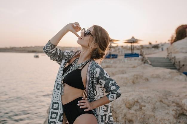 Glückliche junge frau im urlaub, schießen auf den strand im sonnenuntergang, posierend, beißenden finger. tragen eines schwarzen badeanzugs, einer sonnenbrille, einer halskette und einer strickjacke. sonnenuntergang genießen, sommerferien