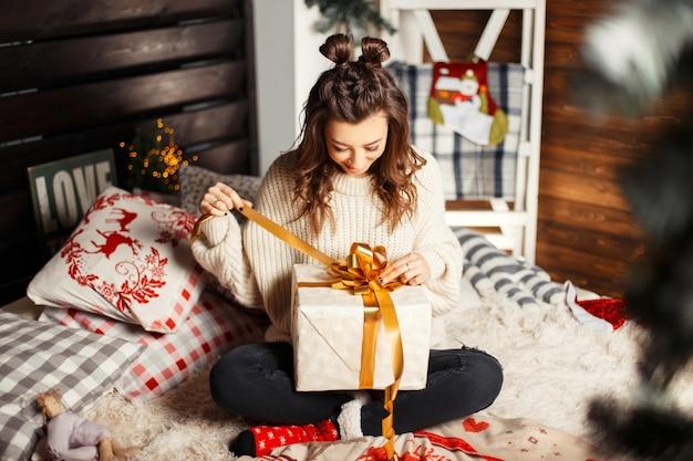 Glückliche junge frau im vintage-strickpullover auf dem bett, das ein geschenk an heiligabend öffnet