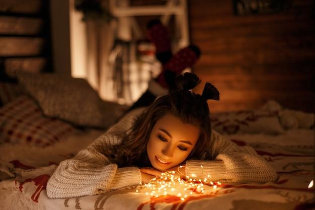 Glückliche junge frau im vintage-strickpullover mit lichtern auf bett
