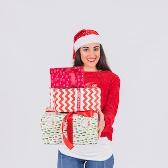 Glückliche junge frau im weihnachtshut und in präsentkartons