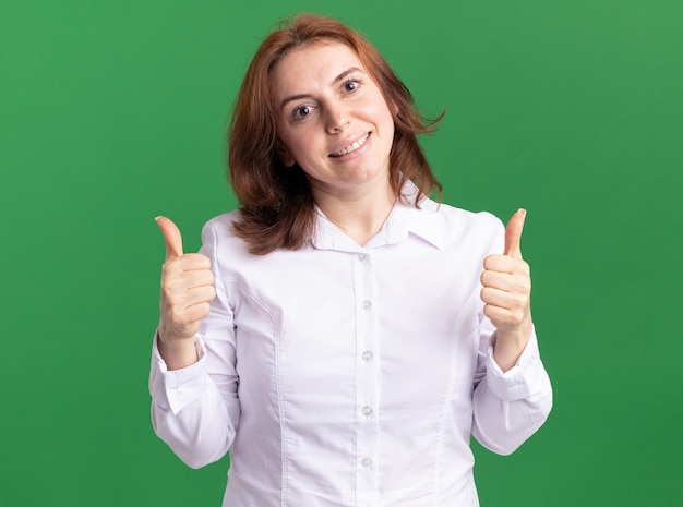 Glückliche junge frau im weißen hemd, das vorne mit lächeln auf gesicht schaut, das daumen oben steht über grüner wand zeigt