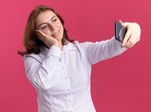 Glückliche junge frau im weißen hemd unter verwendung des smartphones, das das fröhliche stehen des selfies über rosa wand tut