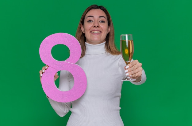 Glückliche junge frau im weißen rollkragenpullover mit der nummer acht und einem glas champagner
