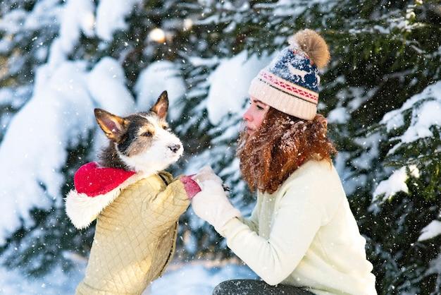 Glückliche junge frau im winter, die im schnee mit ihrem hund spielt