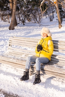 Glückliche junge frau im winter in warmer kleidung in einem schneebedeckten park an einem sonnigen tag sitzt auf den bänken und genießt die frische luft und den kaffee allein