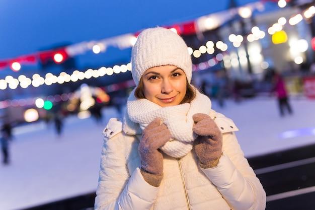 Glückliche junge frau im winter nahe dem eisbahnweihnachts- und winterkonzept