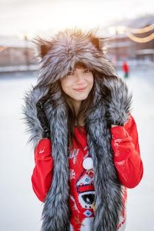 Glückliche junge frau im wolfshut im winter an der eisbahn