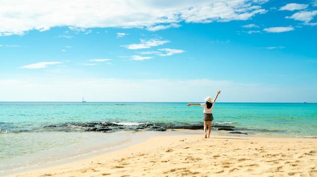 Glückliche junge frau in den weißen hemden und in den kurzen hosen, die am sandstrand gehen. entspannen und urlaub am tropischen paradiesstrand genießen. mädchen in den sommerferien. sommergefühl. glücklicher tag.