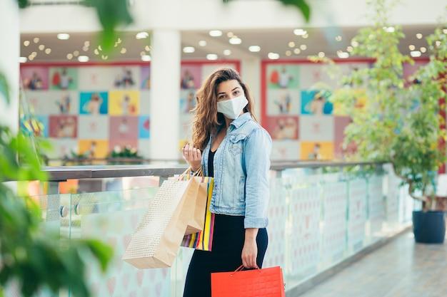 Glückliche junge frau in der medizinischen maske, die im einkaufszentrum mit vielen einkaufstüten in den händen geht.