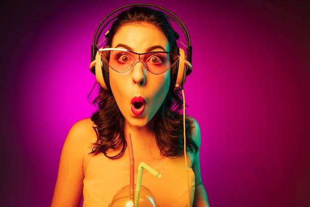 Glückliche junge frau in der roten sonnenbrille, die musik auf trendigem rosa neon trinkt und hört