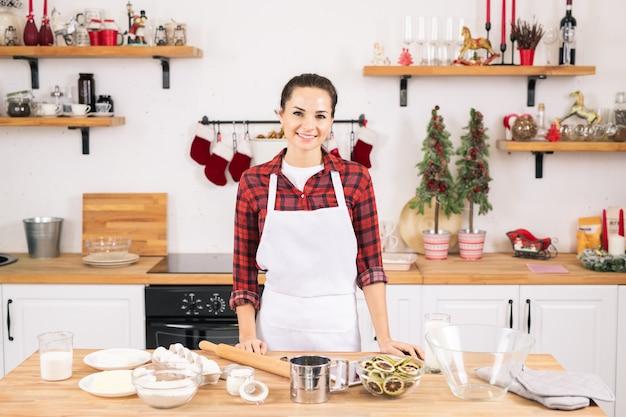 Glückliche junge frau in der schürze, die durch tisch in der küche steht, während kekse gemacht werden