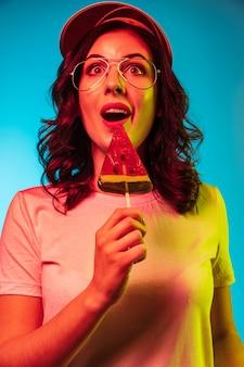 Glückliche junge frau in der sonnenbrille, die süßigkeiten isst und über trendiges blaues neon lächelt