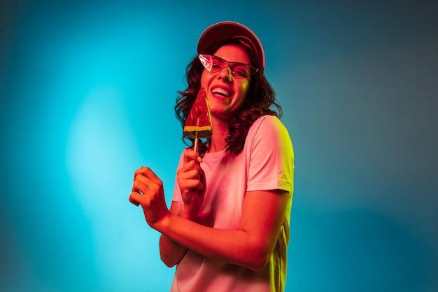 Glückliche junge frau in der sonnenbrille, die süßigkeiten isst und über trendiges blaues neonstudio lächelt
