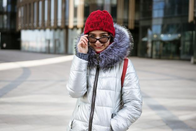 Glückliche junge frau in der sonnenbrille in einer winterjacke mit einem rucksack nahe dem gebäude. reisekonzept