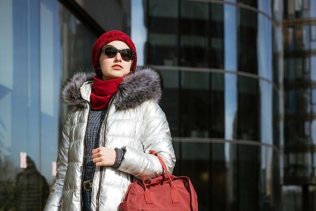 Glückliche junge frau in der sonnenbrille in einer winterjacke mit einem rucksack nahe dem gebäude