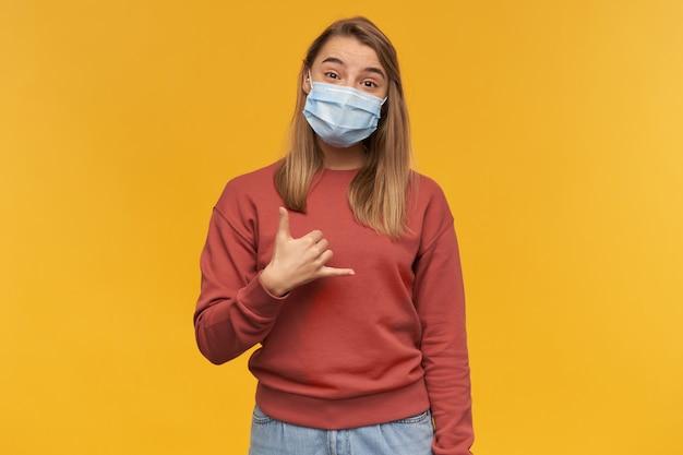 Glückliche junge frau in der virenschutzmaske im gesicht gegen coronavirus, die telefongeste zeigt, die bittet, sie über gelbe wand anzurufen