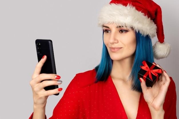 Glückliche junge frau in der weihnachtsmütze mit geschenkbox und smartphone über grauem hintergrund. weihnachts-online-shopping-verkaufskonzept