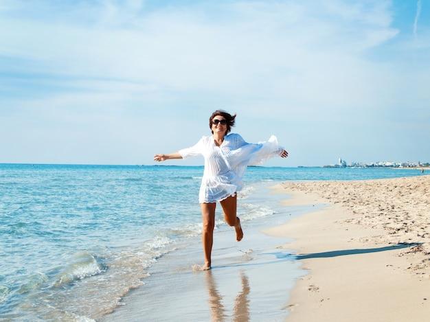 Glückliche junge frau in der weißen vertuschung, die auf dem strand läuft. reise- und urlaubskonzept.