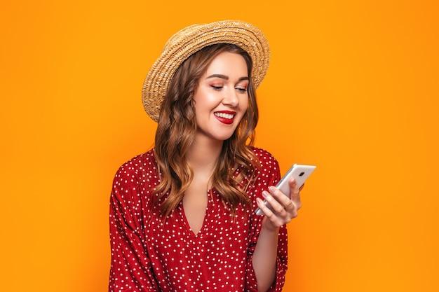 Glückliche junge frau in einem roten kleid des strohhutes mit rotem lippenstift, der ihr handy betrachtet und lokalisiert auf gelber wand lächelt. mädchen liest eine nachricht macht online-einkäufe