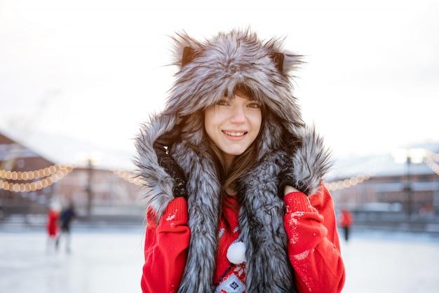 Glückliche junge frau in einem wolfshut im winter auf der eisbahn wirft in einem roten pullover draußen am nachmittag auf
