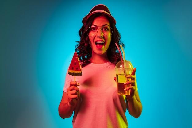 Glückliche junge frau in einer kappe, die süßigkeiten hält und über trendigem blauem neon trinkt