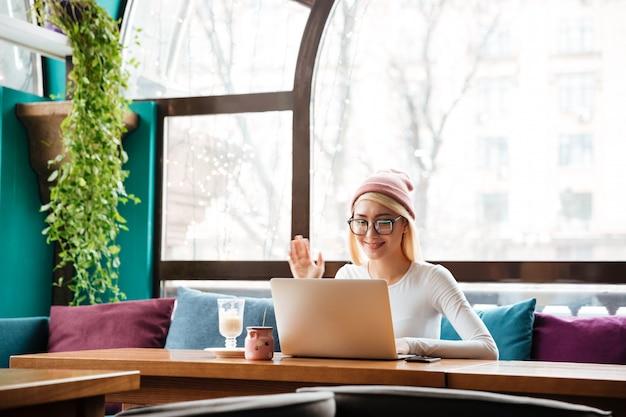 Glückliche junge frau in hut und brille, die laptop-computer für video-chat im café verwendet