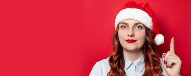 Glückliche junge frau in rotem sankt-hut mit bommel und in einem blauen hemd zeigt geste auf roter wand. kopieren sie platz. saisonale weihnachtsferien rabatte und verkauf.