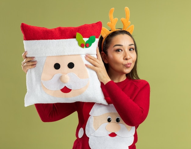 Glückliche junge frau in rotem weihnachtspullover mit lustigem rand mit hirschhörnern, die weihnachtskissen lächelnd über grüner wand halten