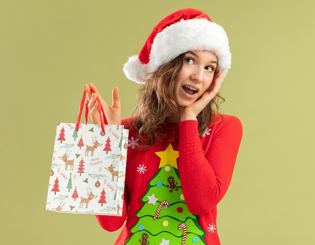 Glückliche junge frau in rotem weihnachtspullover und weihnachtsmütze, die papiertüten mit weihnachtsgeschenken hält und fröhlich über grüner wand lächelt