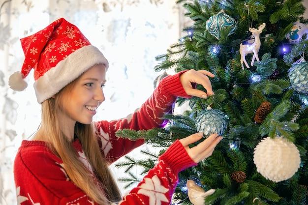 Glückliche junge frau in santa claus hat decorating christmas tree mit flitter