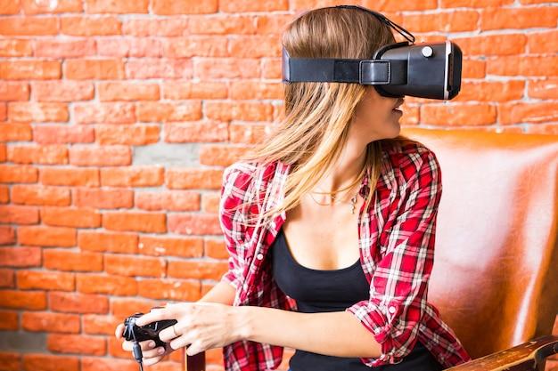 Glückliche junge frau in virtual-reality-headset oder 3d-brille und kopfhörer, die zu hause videospiele mit controller-gamepad spielt playing