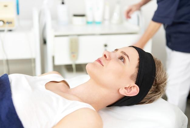 Glückliche junge frau, kunde des kosmetikzentrums auf massagetisch liegend, bereit für kosmetische eingriffe in der professionellen gesichtspflege hautpflegekonzept