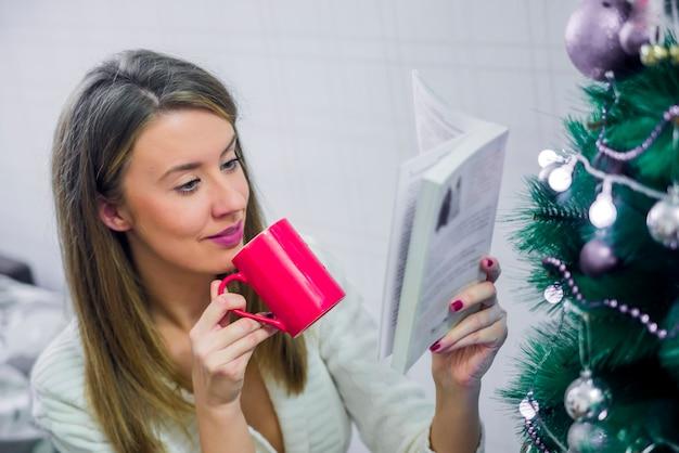 Glückliche junge frau liest buch vor weihnachtsbaum. weihnachtsabend junge schöne blonde frau las buch in klassischen wohnungen, dekoriert baum.