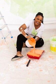 Glückliche junge frau malt die wand mit farbe