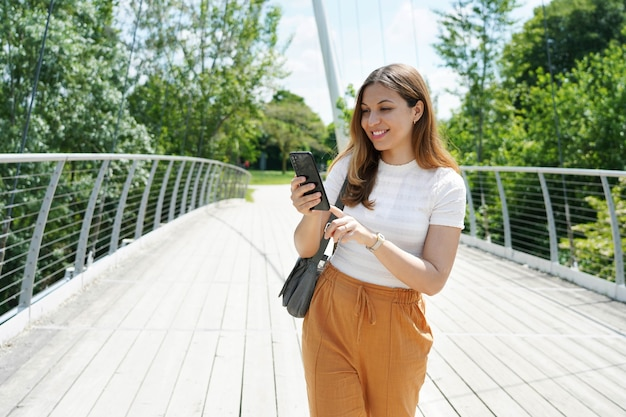 Glückliche junge frau mit bequemer kleidung, die mit dem finger auf dem smartphone im stadtpark tippt. nachhaltiges umweltfreundliches stadt- und lifestyle-technologiekonzept.