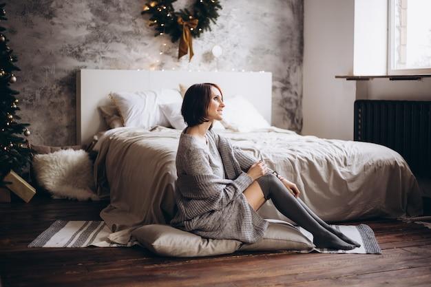 Glückliche junge frau mit bett zu hause im schlafzimmer