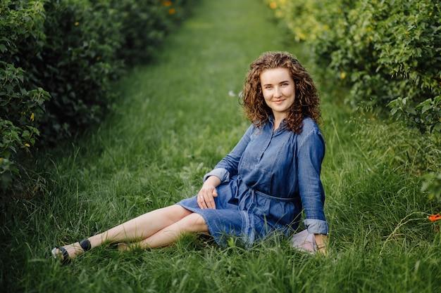 Glückliche junge frau mit braunem lockigem haar, ein kleid tragend, im freien in einem garten posierend