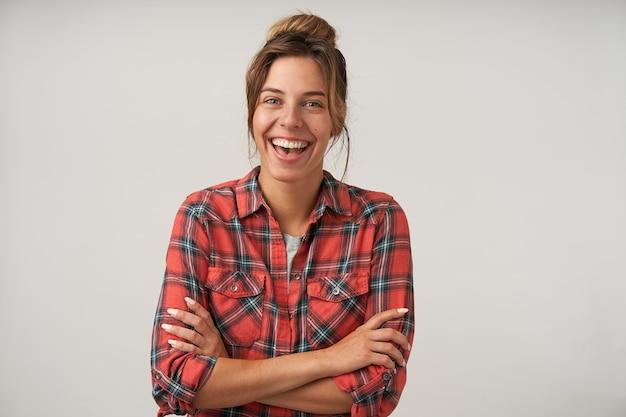 Glückliche junge frau mit brötchenfrisur, die auf weiß aufwirft, freudig lächelnd mit gekreuzten händen auf ihrer brust, positives gefühlskonzept