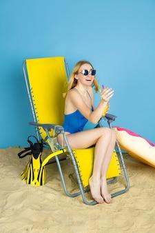 Glückliche junge frau mit cocktail lächelnd, lachend, gruß auf blauem studiohintergrund. konzept der menschlichen gefühle, gesichtsausdruck, sommerferien, wochenende. sommerzeit, meer, meer, alkohol.
